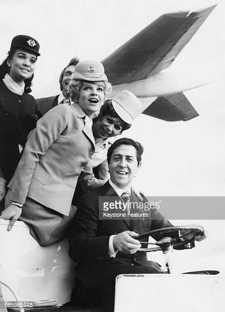 Swiss actor Vico Torriani with stewardesses Emely Schiller of Air France Anke Syring of Pan Am and Silvia Frank of Lufthansa at Berlin Airport...