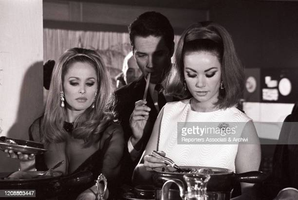 Swiss actress Ursula Andress and French actress Claudine Auger taking a break on the set of Anyone Can Play 1967
