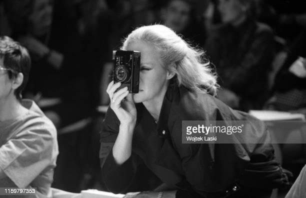 Swiss actress Ursula Andress as a photographer during the Kenzo fashion show, Paris, October, 1983.