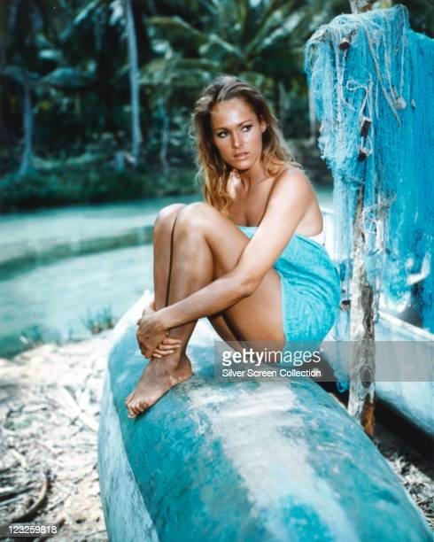 Ursula Andress Swiss actress wrapped in a blue towel sitting on the hull of an upturned boat with blue fishing nets hanging to the right of the image...