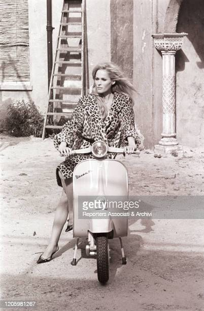 Swiss actress Ursula Andress posing on a Vespa. London, 17th July 1967