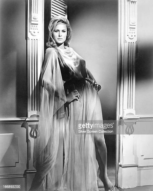 Swiss actress Ursula Andress standing in a doorway wearing a long sheer fabric dress circa 1965