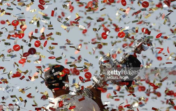 Swiss Alinghi boss Ernesto Bertarelli holds up the America's Cup trophy or 'Auld Mug' after winning the seventh regatta in the bestofnine match...