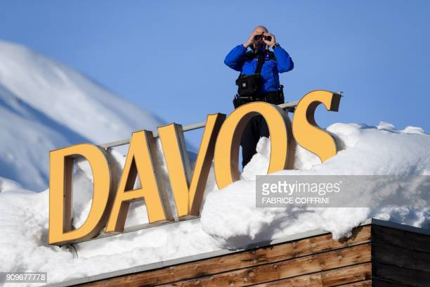 TOPSHOT Swiss armed security personnel stand guard on the rooftop of a hotel next to letters covered in snow reading 'Davos' near the Congress Centre...
