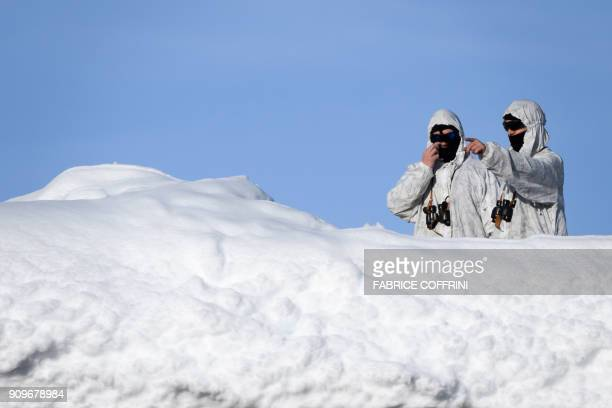 Swiss armed security personnel stand guard on the rooftop of a hotel covered in snow near the Congress Centre of the World Economic Forum on January...