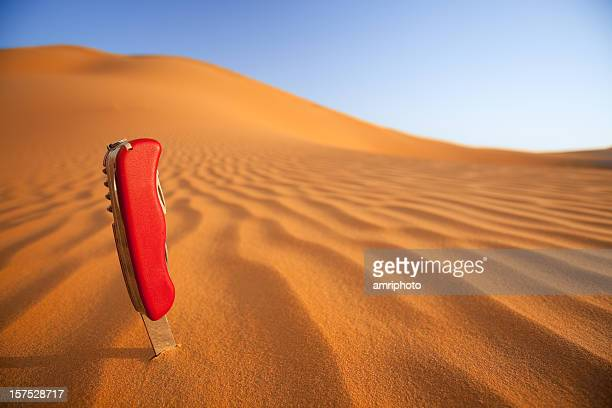 swiss army knife in desert sand