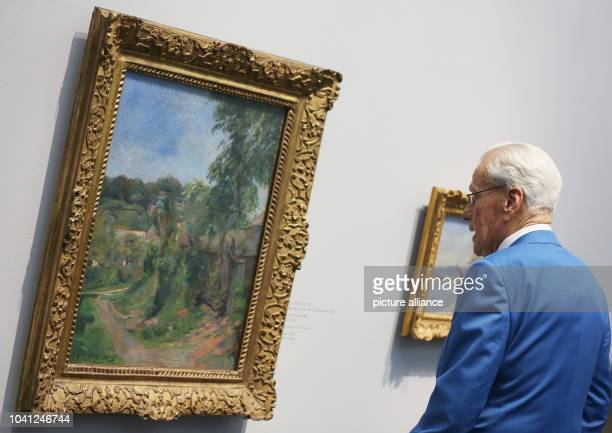 Swiss art collector and donor Gerard J Corboud examines the painting 'Landschaft bei Rouen' by Pail Gauguin in the exhibition 'Along the Seine with...