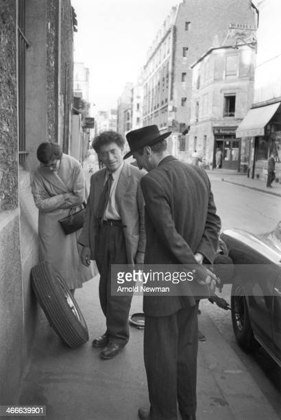 Swiss artist Alberto Giacometti stands on a sidewalk and talks with a man as beside them another man changes the tire on a parked car Paris France...