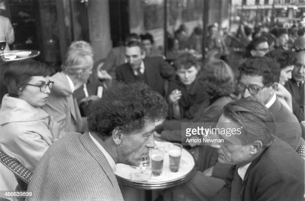Swiss artist Alberto Giacometti talks with another man at a crowded cafe Paris France May 12 1954