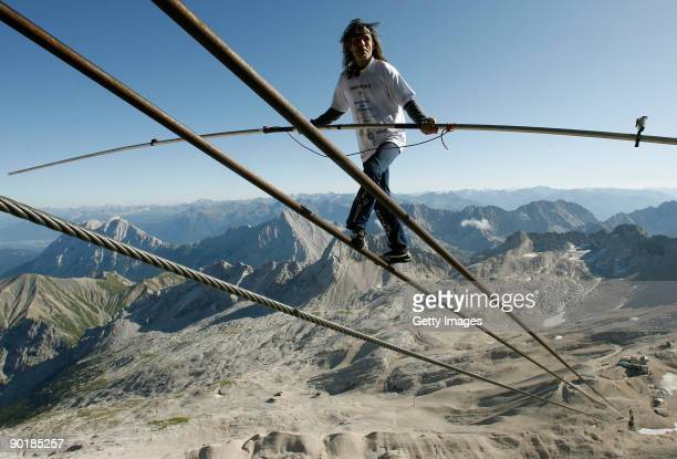 Swiss artist Freddy Nock balances on the cable car ropeway in front of the Alps panorama on top of Germany's highest mountain Zugspitze on August 30...