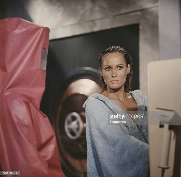 Swiss born actress Ursula Andress pictured in character as Honey Ryder wearing a blue robe in a scene from the James Bond film Dr No at Pinewood...