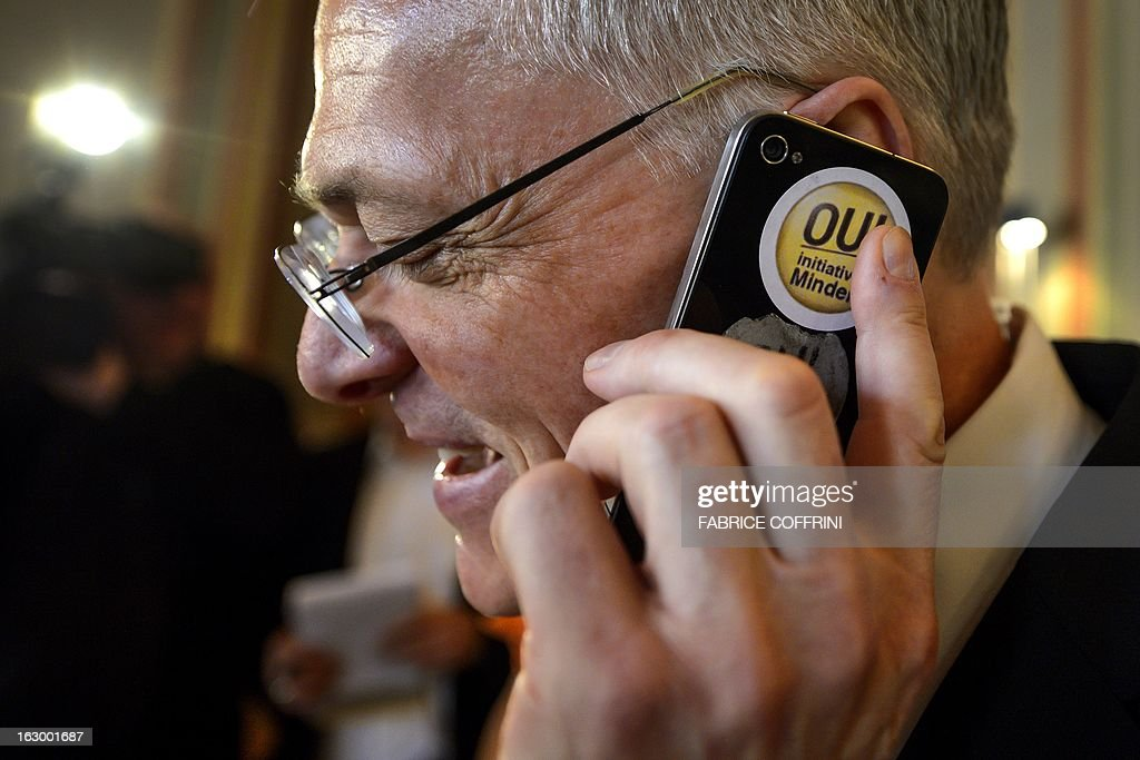 Swiss businessman and senator Thomas Minder uses a mobile phone bearing a sticker reading in French 'Yes Initiative Minder' as waiting for the result on a nationwide vote on March 3, 2013 in Schaffhausen. Switzerland took part in a popular vote on whether to rein in executive pay and force business leaders to give up departure compensation known as golden parachutes. The so-called Minder Initiative, after its sponsor businessman and senator Thomas Minder, already passed with 67.4 percent of votes in favour in Geneva, where voting ended at noon.
