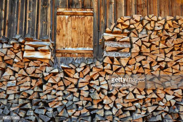Swiss chalet or hut with firewood neatly stacked against wall with closed shutter window. Grindelwald, Switzerland