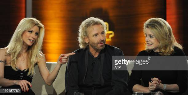 Swiss copresenter Michelle Hunziker gestures beside of German TV host Thomas Gottschalk and French actress Catherine Deneuve on stage during the...