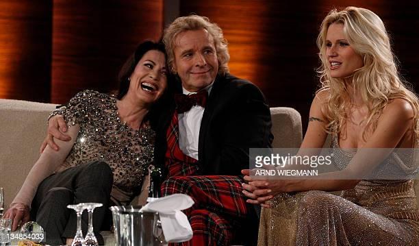 Swiss copresenter Michelle Hunziker sits beside as German TV show host Thomas Gottschalk hugs German actress Iris Berben during the German TV game...