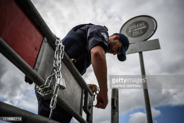 Swiss customs officer attaches a chain to a fence after opening the Swiss-French border on June 14, 2020 in Thonex near Ambilly, France. - The Swiss...