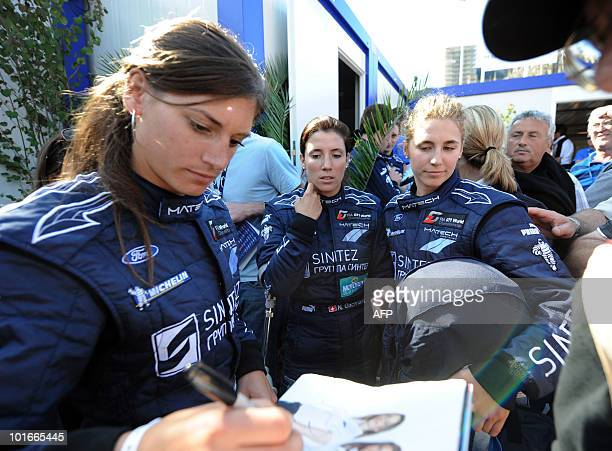 Swiss Cyndie Allemann Natacha Gaghnang and Rahel Frey drivers of a Ford GT sign autographs on June 6 2010 in Le Mans western France Fiftysix cars...