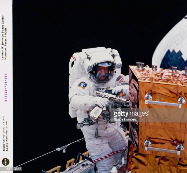Swiss ESA astronaut Claude Nicollier works at a storage enclosure, using one of the Hubble Space Telescope's power tools during the second of three...