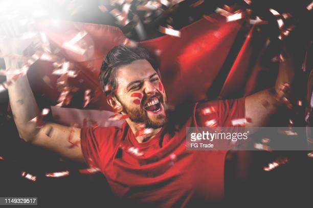 swiss fan celebrating with the national flag - fan enthusiast stock photos and pictures