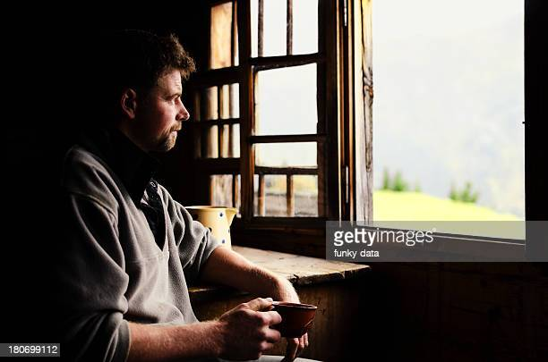 swiss farmer staring out of window - hut stock pictures, royalty-free photos & images