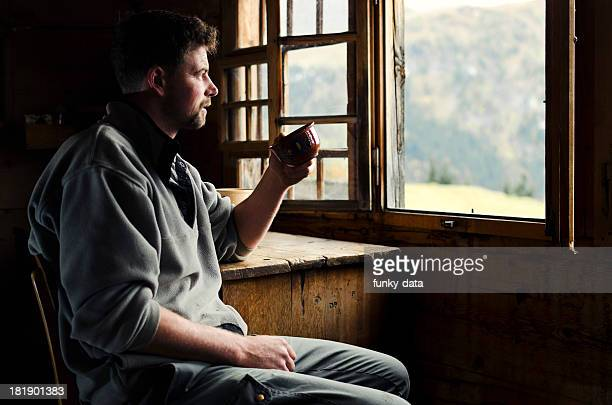 swiss farmer with his morning coffee watching alps - shack stock pictures, royalty-free photos & images