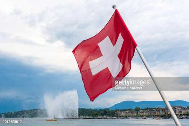 swiss flag and jet d'eau in geneva, switzerland - genève zwitserland stockfoto's en -beelden
