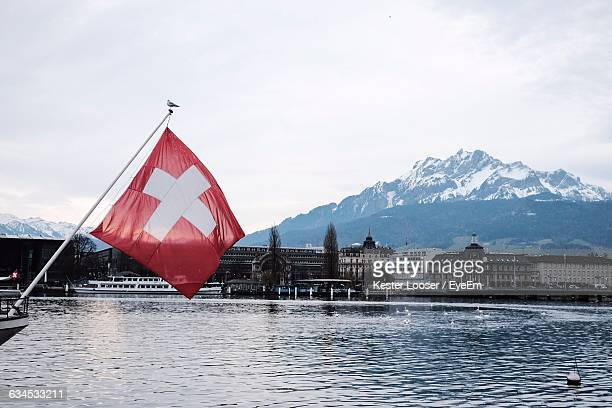 Swiss Flag By River Against Mountain And Sky During Winter