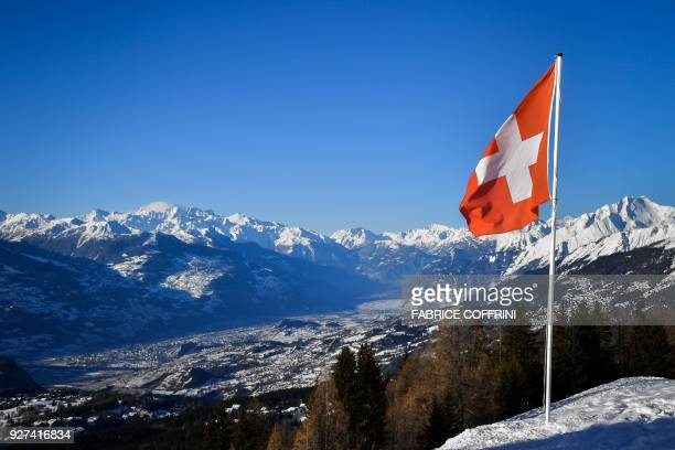 A Swiss flag floats above the Rhone's valley in the Swiss canton of Valais place of Sion 2026 bid to the Winter Olympic Games on March 4 2018 in...