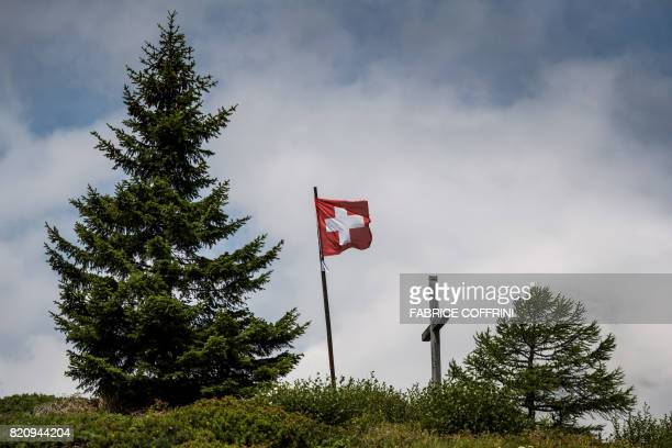 A Swiss flag floats at the top of the Simplon Pass on July 21 2017 / AFP PHOTO / Fabrice COFFRINI