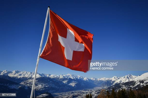 A Swiss flag flutters on March 4 2018 in CransMontana above the Rhone valley in the Swiss canton of Valais location of Sion a city of some 34000...