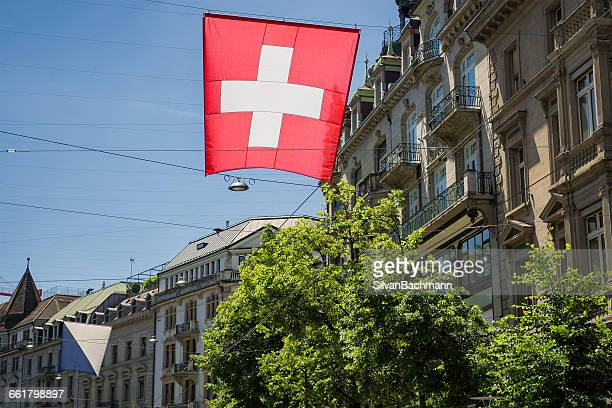 Swiss flag flying in streets of Zurich, Switzerland