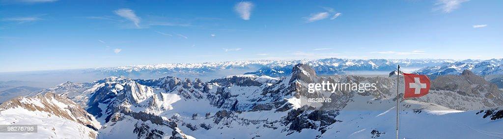 Bandera suiza en el viento (XXL) con vista panorámica de las montañas : Foto de stock