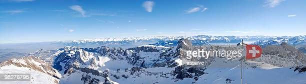 swiss flag in the wind over panoramic mountain view (xxl) - switzerland stock pictures, royalty-free photos & images