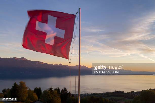 A Swiss flag is seen floating at sunset above Lake Geneva on October 5 2017 from the Mont de Gourze in Riez western Switzerland / AFP PHOTO / Fabrice...