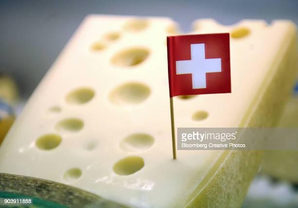 a swiss flag is seen in a piece of emmenthaler cheese - zwitserse kaas stockfoto's en -beelden