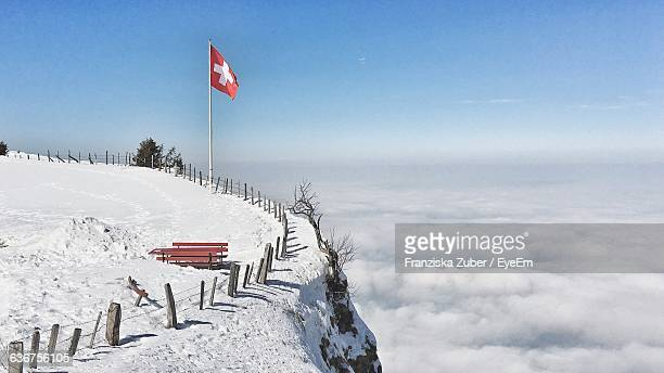 Swiss Flag On Snow Covered Mountain By Cloudscape