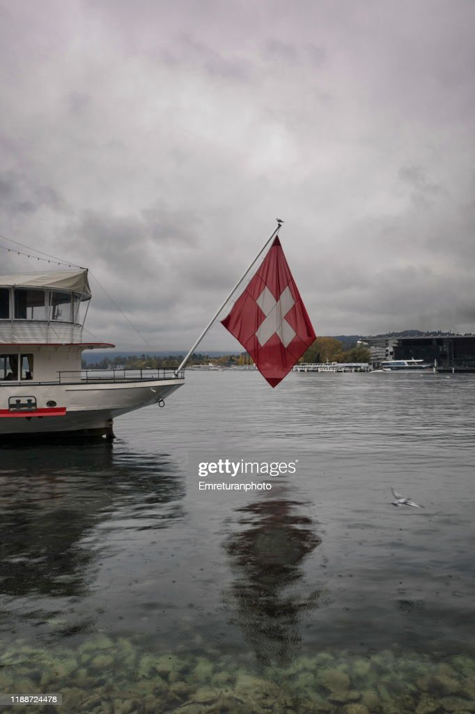 Swiss flag on the pole of a cruise boat in lake Lucerne. : Stock Photo