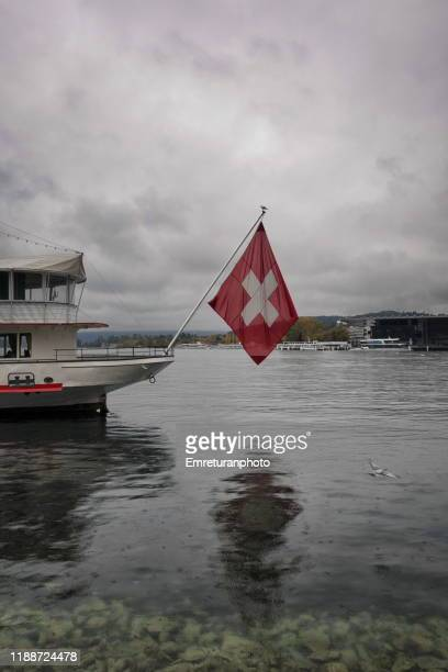 swiss flag on the pole of a cruise boat in lake lucerne. - emreturanphoto stock pictures, royalty-free photos & images