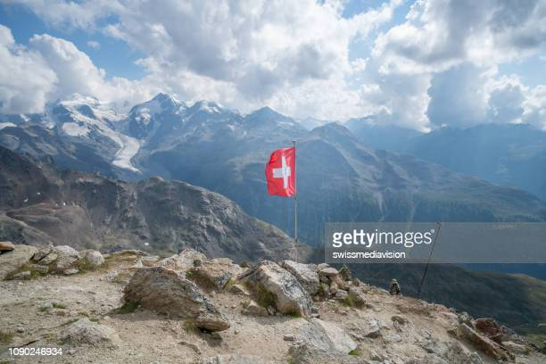 swiss flag on top of beautiful mountain landscape in the swiss alps in graubunden canton - switzerland stock pictures, royalty-free photos & images