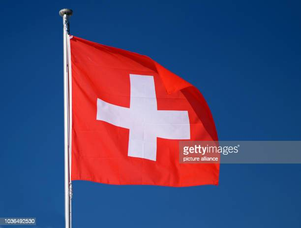 A Swiss flag sways on a pole in the Wallis mountain region on top of the Eggishorn mountain near Fiesch Switzerland 6 February 2014 The people of...