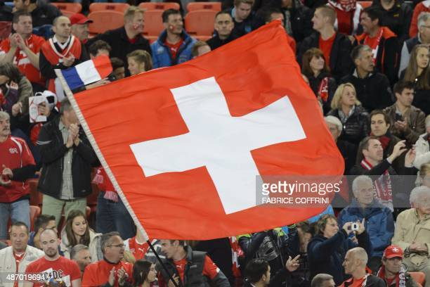 A Swiss flag with a small French flag on its top floats prior to the Euro 2016 qualifying football match between Switzerland and Slovenia at the St...