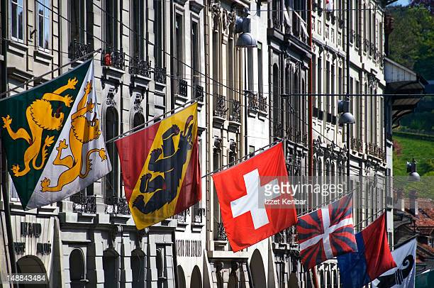 Swiss flags flying from row of Old City buildings.