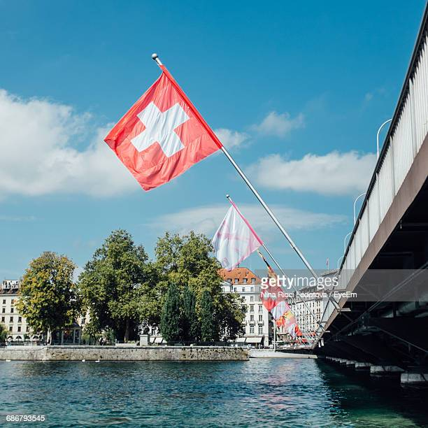 Swiss Flags In Row On Bridge Over River In City