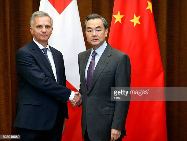 Swiss Foreign Minister Didier Burkhalter left and Chinese Foreign Minister Wang Yi right shake hands before a bilateral meeting at the Ministry of...
