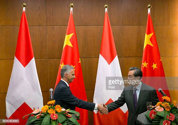 Swiss Foreign Minister Didier Burkhalter left shakes hands with Chinese Foreign Minister Wang Yi right after a joint press conference at the Ministry...