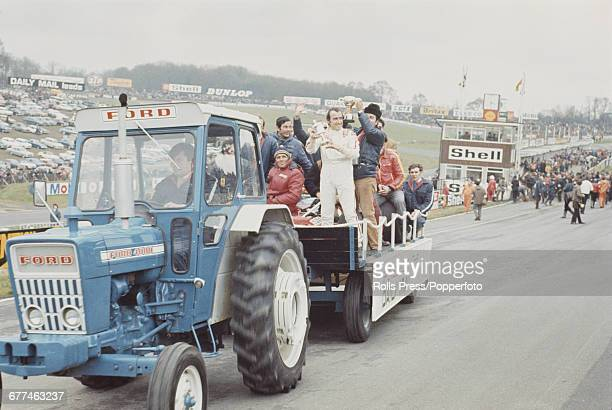 Swiss Formula 1 racing driver Clay Regazzoni holds up his trophy as he rides on a trailer pulled by a tractor around the Brands Hatch motor racing...