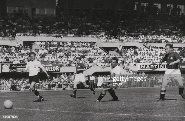 Swiss forward Josef Hugi II scores a goal as teammate forward Charles Antenen Austrians defenders Leopold Barschandt and Gerhard Hanappi look on...