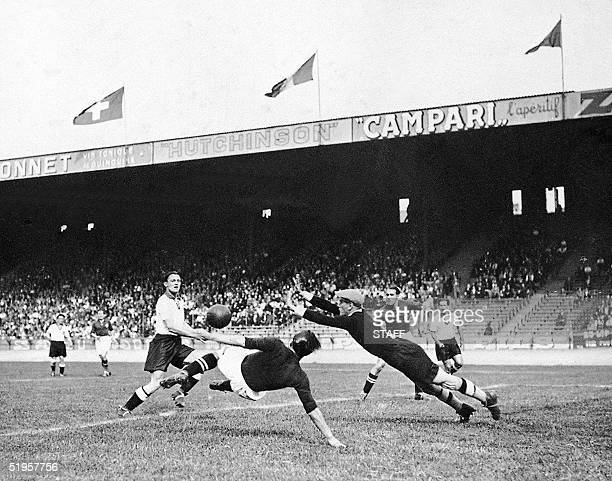 Swiss forward Lauro Amado tries to kick the ball past German goalkeeper Rudi Raftl as forward Andre 'Trello' Abegglen looks on during the World Cup...