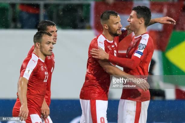 Swiss foward Haris Seferovic is congratulated by Swiss defender Fabian Schaer next to Swiss midfielder Xherdan Shaqiri during the FIFA World Cup WC...