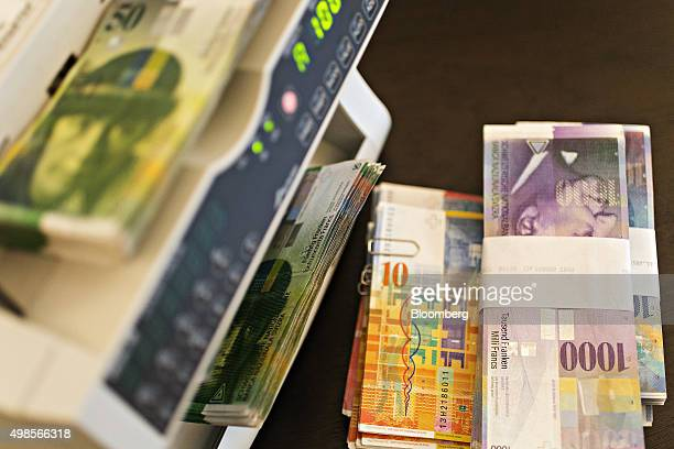 Swiss Franc banknotes sit bundled as a money counting machine counts 50 Swiss franc banknotes in this arranged photograph in the office of a bank in...